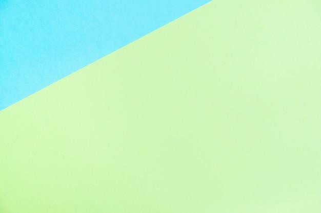 O plano de papel colorido da cor pastel coloca a vista superior, a textura do fundo, o azul e o verde.