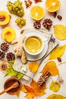 O plano do outono coloca: chá, frutos do outono e decorações em um fundo branco.