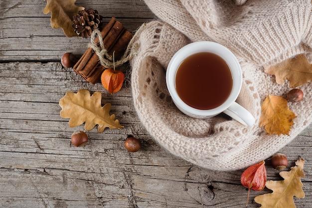 O plano do outono coloca na tabela de madeira com um copo do chá e nas folhas amarelas secas caídas.