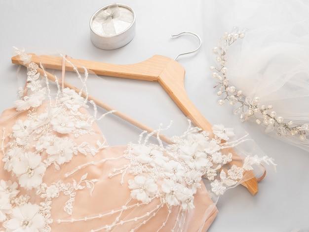 O plano mínimo coloca com o vestido de casamento no gancho e no véu com os grânulos no fundo claro.