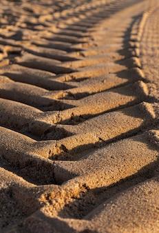 O pneu de carro imprime na areia durante o dia, foco seletivo.