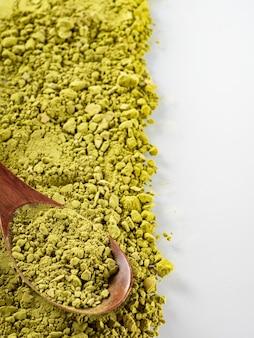 O pó de chá matcha de cor verde está espalhado sobre um fundo branco. copie o espaço.