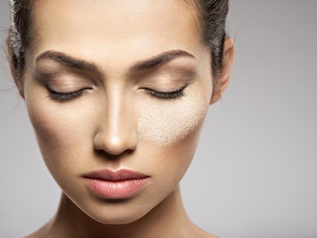 O pó de maquiagem cosmético seco está no rosto feminino. conceito de tratamento de beleza. garota faz maquiagem.