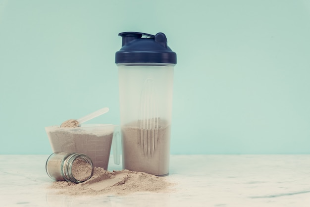 O pó dobro da proteína do whey do chocolate scoop o halterofilismo saudável do alimento da nutrição.