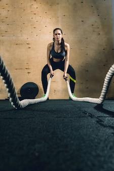 O poderoso treinador muscular atraente crossfit da mulher faz exercícios de batalha com cordas