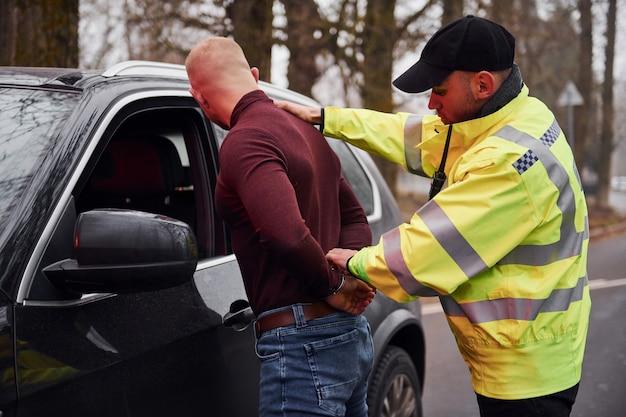 O policial de uniforme verde detém o agressor perto do carro ao ar livre.