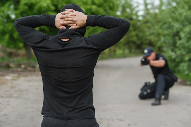 O policial está mirando um terrorista. o agressor está de joelhos, com as mãos cruzadas sobre a cabeça.
