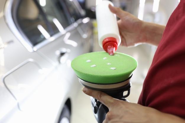 O polidor macho aplica cera protetora na máquina de polimento do carro, removendo arranhões e arranhões Foto Premium