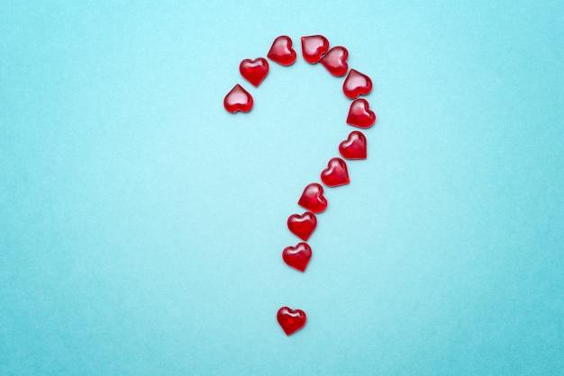 O ponto de interrogação na forma de corações vermelhos em um fundo azul