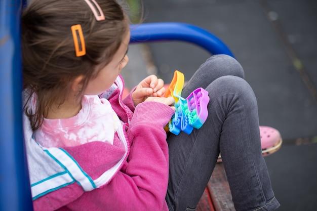 O popular brinquedo colorido anti-stress toque fidget push pop-lo nas mãos de uma criança.