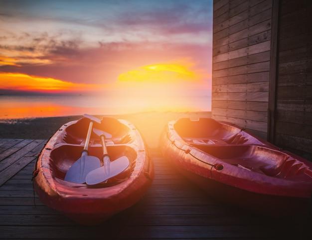 O por do sol bonito com o barco vermelho do caiaque dos pares com configuração do sol.