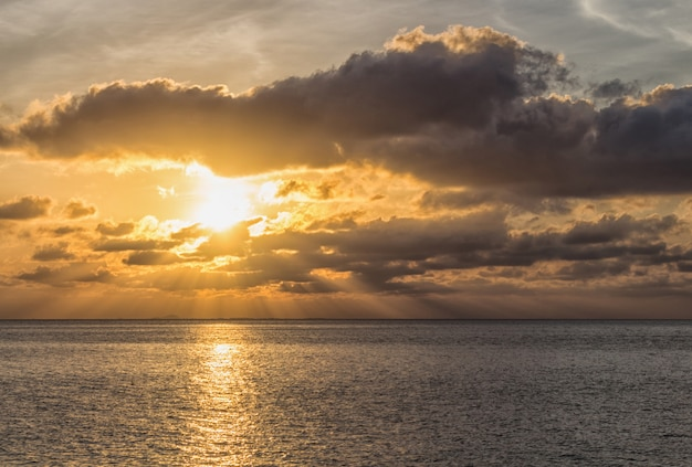 O por do sol bonito sobre o mar com o sol irradia através das nuvens.