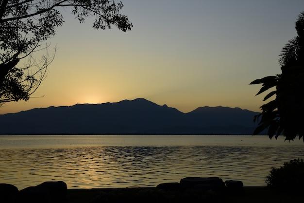 O por do sol com a montanha e o lago em kwan phayao.