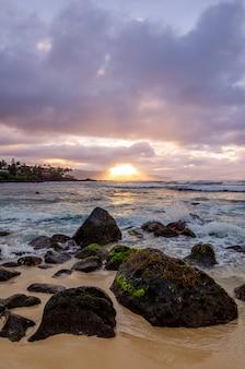 O por do sol que quebra através das nuvens como as ondas espirra em rochas no parque da praia das partes superiores em oahu,