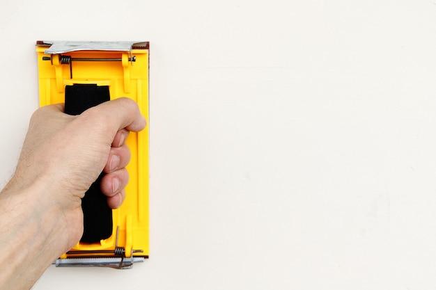 O porta-lixa amarelo na mão na parede branca com espaço de cópia.