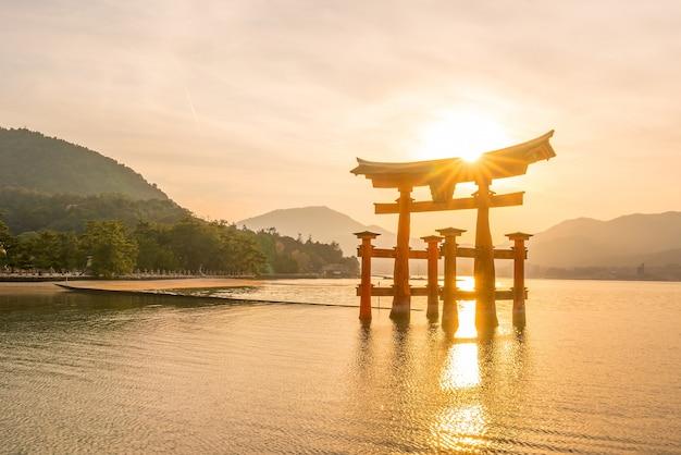 O portão flutuante do santuário de itsukushima ao pôr do sol em miyajima, hiroshima, japão