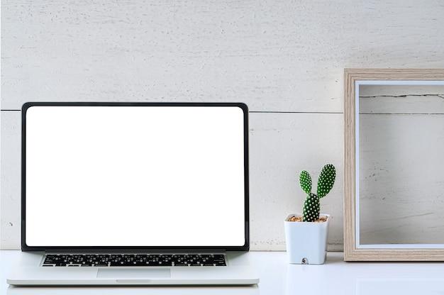 O portátil branco da tela vazia, a moldura para retrato de madeira e o cacto verde florescem na tabela branca.