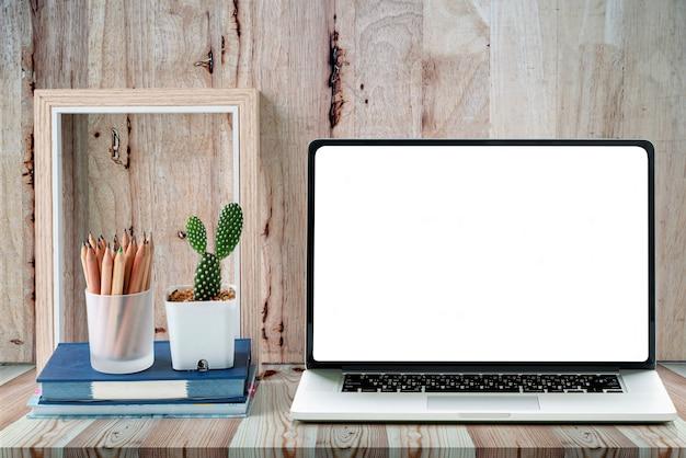 O portátil branco da tela vazia, a moldura para retrato de madeira e o cacto verde florescem na tabela de madeira.