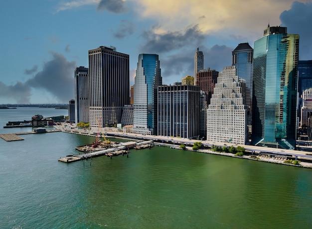 O porto da cidade de nova york em um rio a leste contra o horizonte de manhattan mais alto e majestoso com o pôr do sol