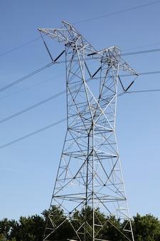 O poste de alta tensão no céu azul