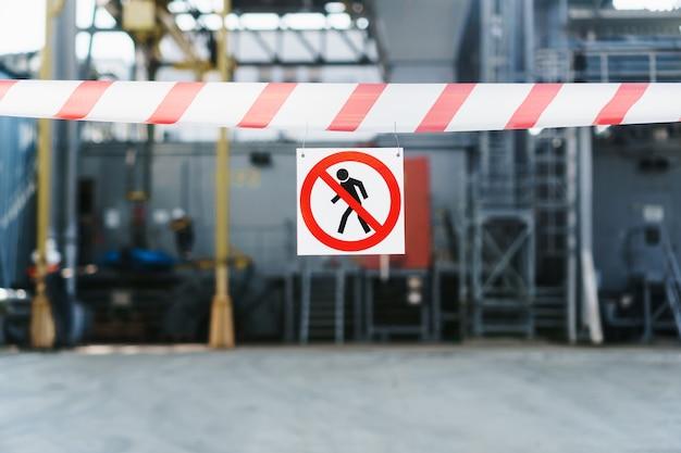 O pôster não é permitida a invasão de uma fita vermelha e branca que cerca a passagem contra o fundo das tubulações da usina.