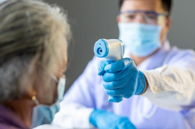 O posto de verificação do coronavírus, os médicos verificam a temperatura da paciente idosa que corre o risco de infecção pelo vírus corona [covid-19].