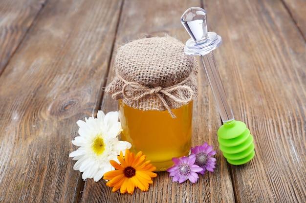 O pote cheio de mel fresco delicioso e flores silvestres na mesa de madeira