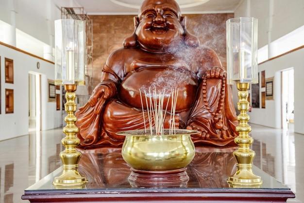 O pote de incenso dourado em frente às estátuas de buda risonhas de mármore no templo na ilha de batam