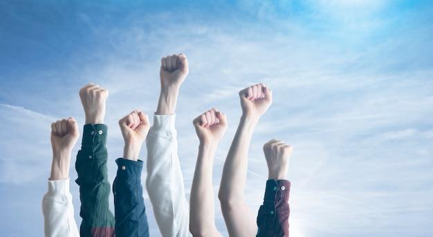 O povo com as mãos erguidas e os punhos no ar, como símbolo de protesto pela igualdade. liberdade.