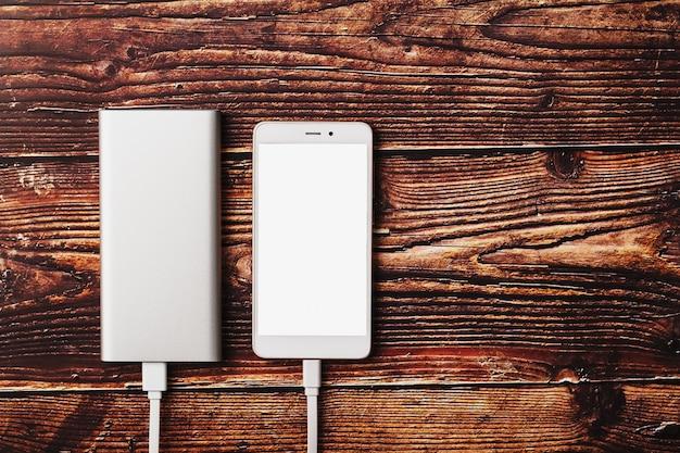 O power bank cobra um smartphone em um fundo de madeira.