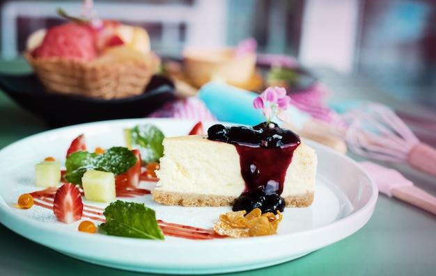 O prato de bolo de queijo de mirtilo colocar na mesa, luz embaçada em torno de
