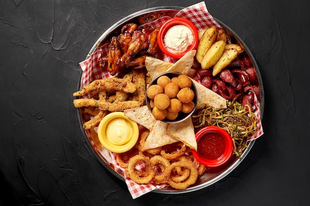 O prato de cerveja com picante asas de frango lula rodelas de batatas fritas rodelas de cebola bolinhas de queijo tártaro à milanesa ...