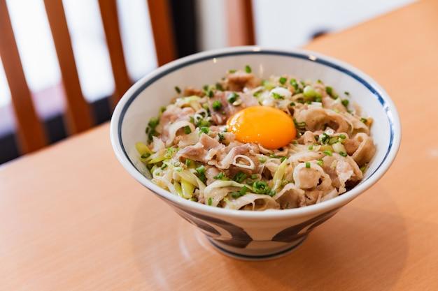 O prato de tigela de arroz japonês que consiste em carne de porco e cebola chiou junto e serviu em cima de arroz