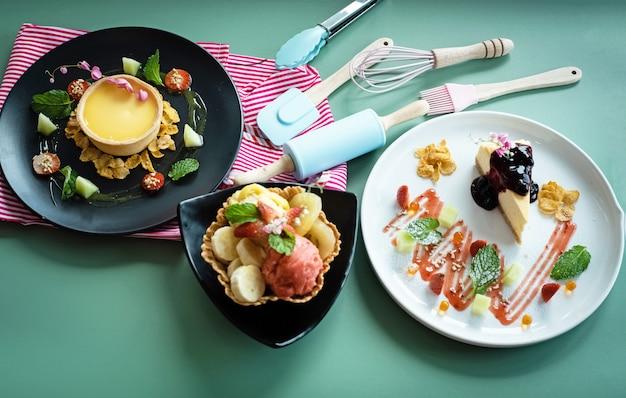 O prato de torta de limão, sorvete de frutas na cesta de waffle e prato de bolo de queijo na mesa