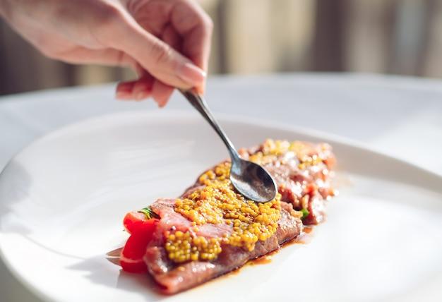 O prato é carpaccio. chef estrume granulado prato de mostarda, carpaccio.