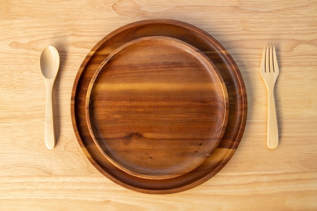 O prato redondo de madeira de acácia e verniz de laca é empilhado em duas camadas e as colheres e os garfos são colocados em um bloco de corte de madeira de borracha no conceito de utensílio de cozinha.