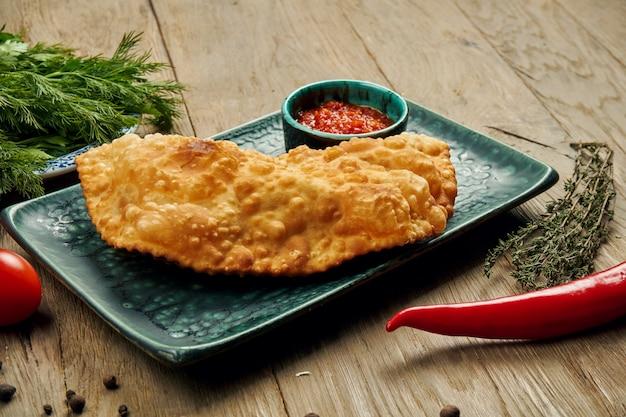 O prato tradicional caucasiano é cheburek, uma torta frita de inoil com diferentes recheios, principalmente carne ou queijo em um prato azul.