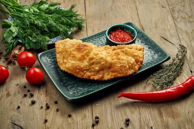 O prato tradicional caucasiano é cheburek, uma torta frita de inoil com recheios diferentes, principalmente carne ou queijo em um prato azul.