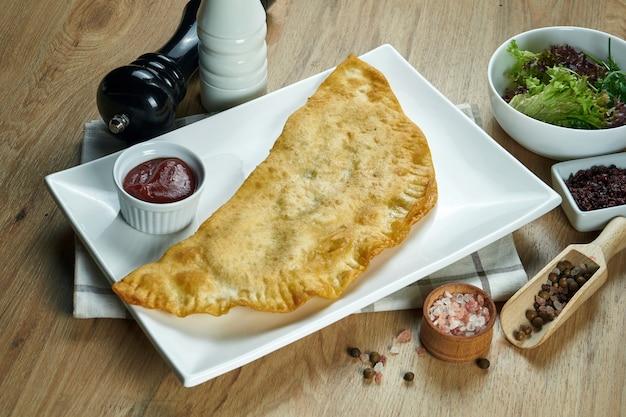 O prato tradicional caucasiano é cheburek, uma torta frita na manteiga com recheios diferentes, principalmente carne ou queijo em um prato branco. lay plana de alimentos