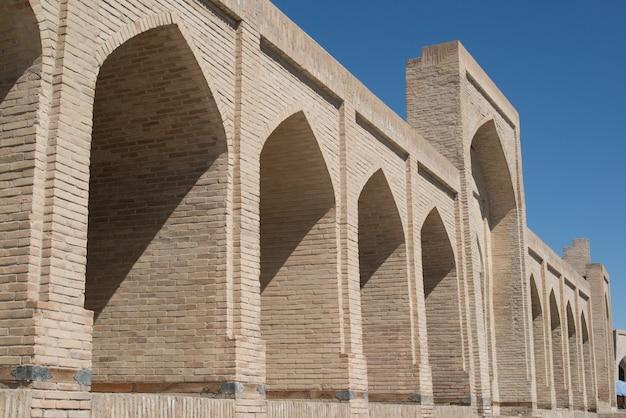 O prédio antigo, a parede com arcos. edifícios antigos da ásia medieval. bukhara, uzbequistão