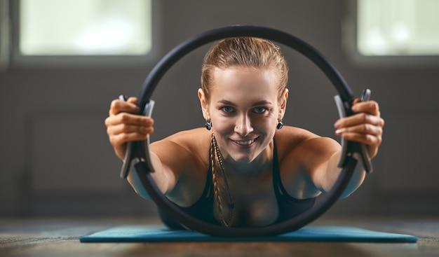 O preparador físico mostra exercícios com um expansor de anel, de manhã na sala de fitness. copie o espaço, motivador de fitness.