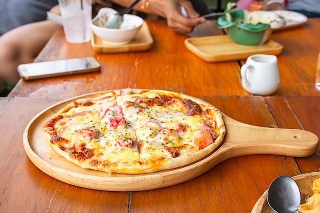 O presunto da pizza na bandeja de madeira é colocado na tabela.