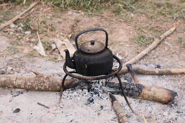 O preto de alumínio velho da obscuridade da chaleira ferve em lenha ardente.
