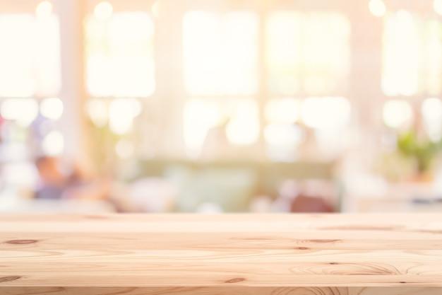O primeiro plano do tampo da mesa de madeira com fundo borrado da loja e do restaurante do café interno para produtos exibe banner de publicidade de montagem.