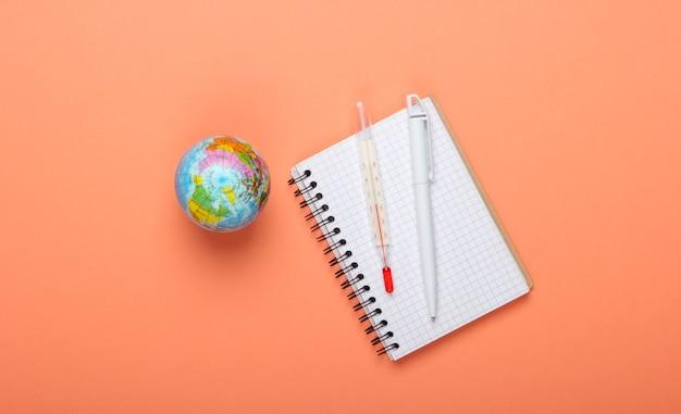 O problema do aquecimento global. globo, termômetro com um caderno em fundo laranja. vista do topo