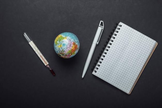 O problema do aquecimento global. globo, termômetro com um caderno em fundo preto. vista do topo