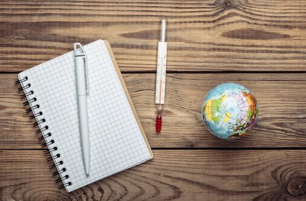 O problema do aquecimento global. globo, termômetro com um caderno na mesa de madeira. vista do topo