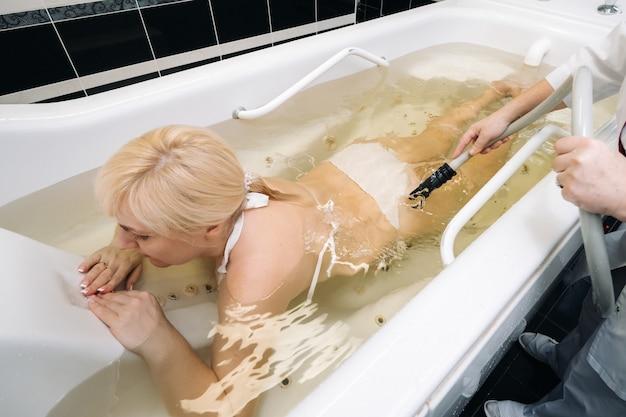 O procedimento de massagem subaquática no banheiro. menina no procedimento de massagem subaquática.