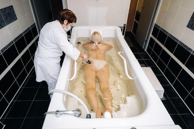 O procedimento de massagem subaquática no banheiro.