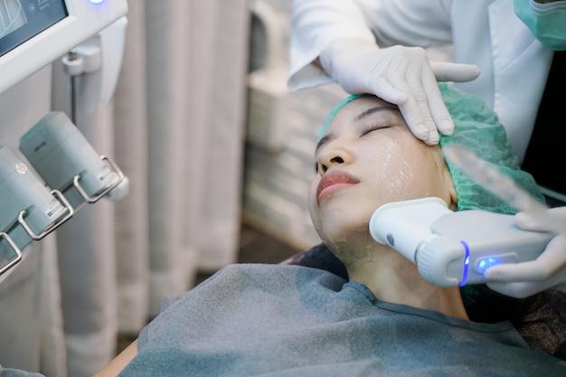 O procedimento de tratamento com laser ou frequência de aperto da pele envolve a mulher jovem que recebe o queixo a laser.